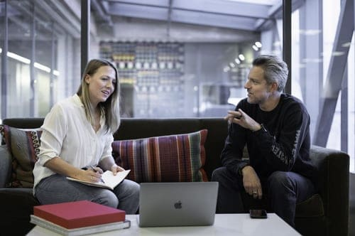 two people sitting on the couch while talking